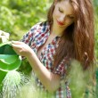 Portrait of an attractive female water plants with a watering ca - ストック写真