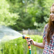 Stock Photo: Summer garden grass womplay with water hose sunny day