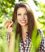 Woman with apple in garden — Stock Photo