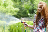 Summer garden grass woman play with water hose sunny day — Stock Photo