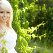 Close-up portrait of beautiful young blond woman in white blouse — Stock Photo