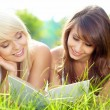 Stock Photo: Two young beautiful smiling women reading book, sitting on grass