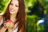 Portrait long-haired woman hands red apple background summer p — Stock Photo