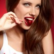 Happy woman with cherries over red — Stock Photo