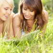 Two young beautiful smiling women reading book, sitting on grass — Stok fotoğraf