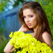 Woman holding yellow flowers . outdoor shoot — Stock Photo #11755719