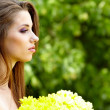 Woman holding yellow flowers . outdoor shoot — Stock Photo #11755769