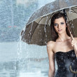 Beautiful woman holding umbrella out in the rain — Stock Photo
