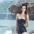 Beautiful woman holding umbrella out in the rain — Stock Photo #11989029