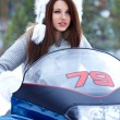Smiling young woman riding a snowmobile — Stock Photo #12048409