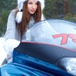 Smiling young woman riding a snowmobile — Stock Photo #12048459
