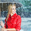 Beautiful blonde woman holding umbrella out in the rain — Stock Photo #12121282