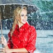 Beautiful blonde woman holding umbrella out in the rain — Stock Photo