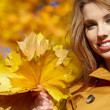 Beautiful elegant woman standing in a park in autumn — Stock Photo