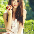 Apple woman. Very beautiful ethnic model eating red apple in the - Stock Photo