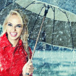 Beautiful blonde woman holding umbrella out in the rain — Stock Photo #12293735