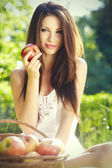 Apple woman. Very beautiful ethnic model eating red apple in the — Stock Photo