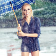 Sexy girl under umbrella watching the rain — Stock Photo