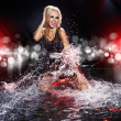 Saxy woman dancing in water on black , — Stock Photo