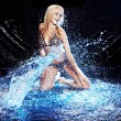 Saxy woman dancing in water on black , — Stockfoto