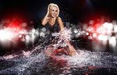 Saxy woman dancing in water on black , — Stock Photo