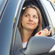 Young lady in a car showing key — Stockfoto