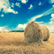 Straw bales on farmland with blue cloudy sky — Stock Photo