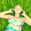 Young woman with headphones on the field — Stock Photo #12025470