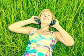 Giovane donna con cuffie sul campo — Foto Stock