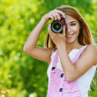 Smiling young woman with camera - Stock Photo