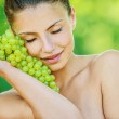 Woman with bare shoulders holding grapes — Stock Photo #10739903
