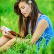 Woman sitting on grass and reading book — Stock Photo #10739907