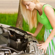 Young woman repairing car - Stock Photo