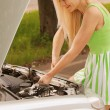 Young woman repairing car - Stock fotografie