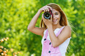 Smiling young woman with camera — Stock Photo
