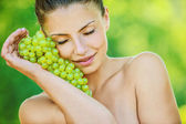 Woman with bare shoulders holding grapes — Stock Photo