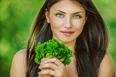 Woman with bare shoulders holding bunch of parsley — Stock Photo