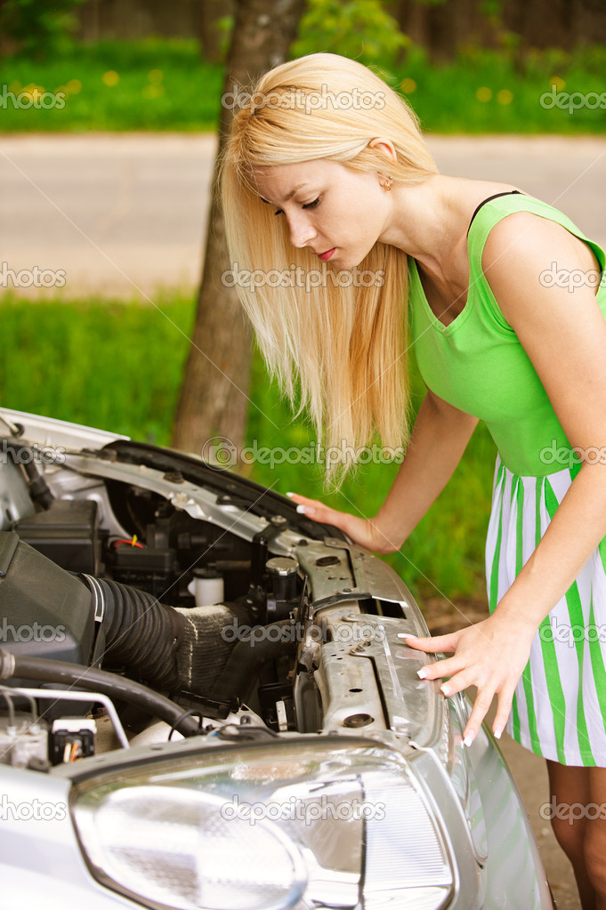 Nice young woman repairing car, against green of summer park. — Stock Photo #10739995