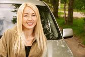 Ung kvinna ler om bilen — Stockfoto