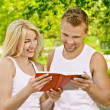 Smiling couple dressed in white reading book - Stock Photo