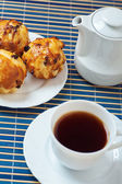 Muffins on plate, jug of milk and cup of tea — Stock Photo