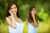 Zwei hübsche Mädchen reden auf Handy — Stockfoto