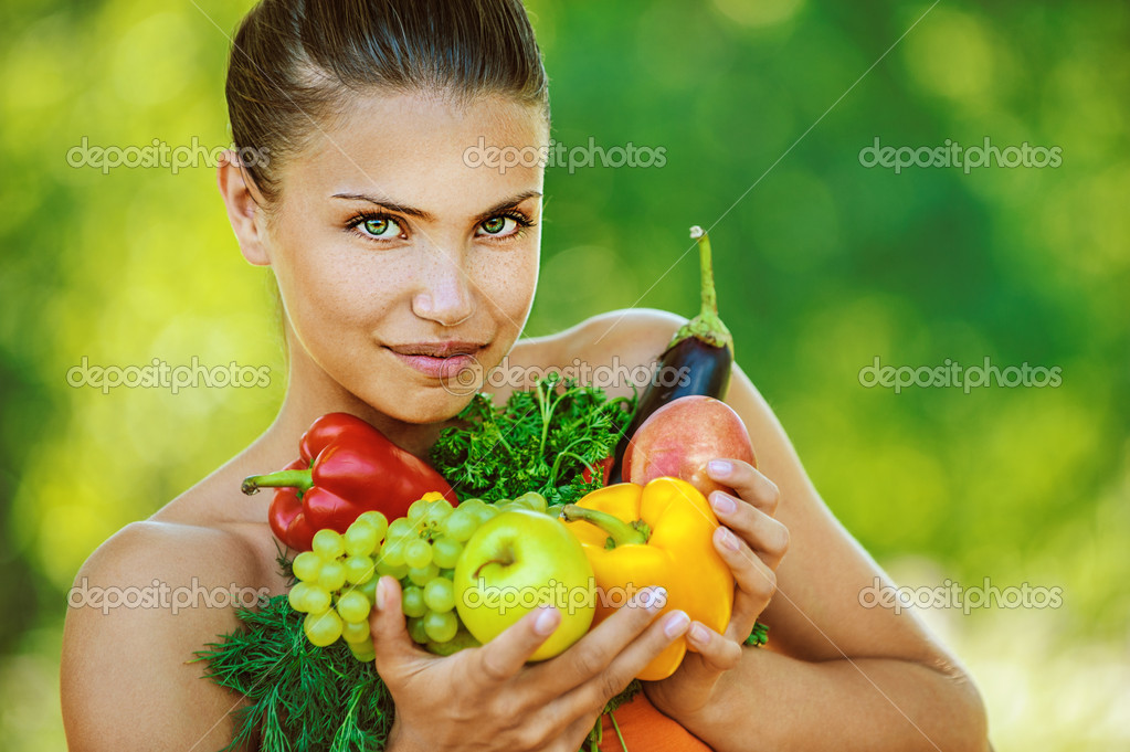 Portrait of young beautiful woman with bare shoulders holding fruit and vegetables - peppers, apples, eggplant, parsley, grapes, on green background summer nature.  Stock Photo #10784522