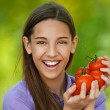 Smiling teenage girl holding red tomatoes — Stock Photo #11372080