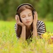 Woman listening to music through headphones - Stock Photo