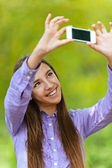 Teenage girl pictures of himself with smartphone — Stock Photo