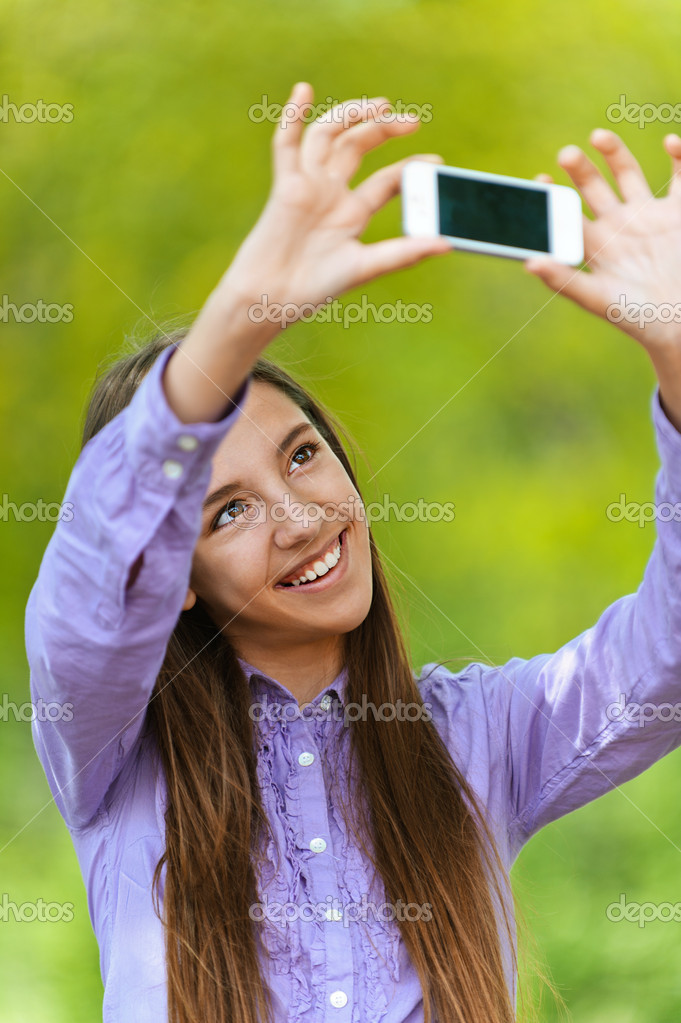 Smiling teenage girl pictures of himself with smartphone, against green of summer park.  Stock Photo #11372083
