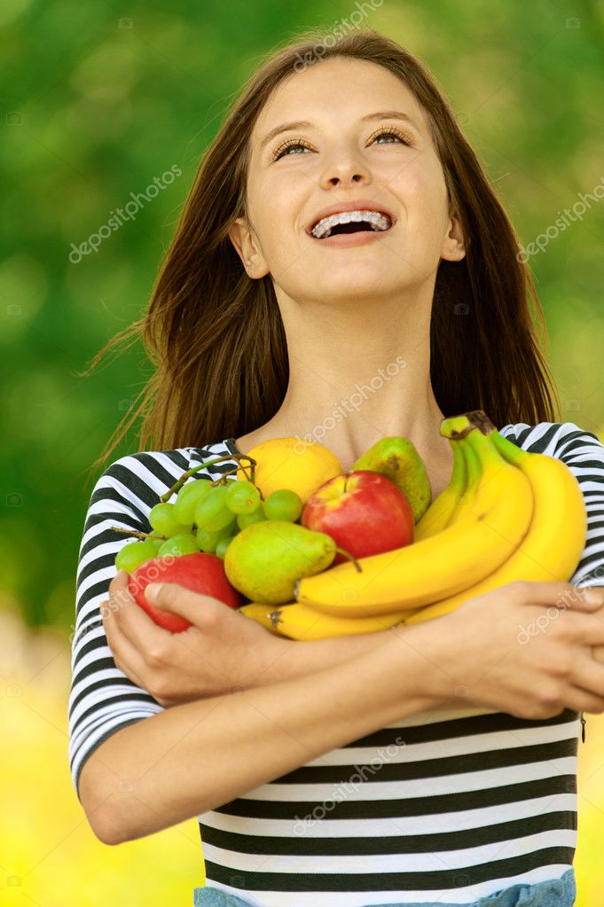 Young attractive woman holding apples, pears, grapes and bananas, against green of summer park. — Stock Photo #11372103