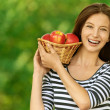 Woman holding basket with apples — Stock Photo