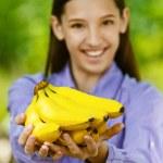 Smiling teenage girl shows yellow bananas — Stock Photo #11779302